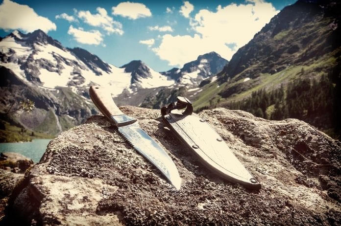 One of the best Bowie knives sitting on a rock overlooking a beautiful mountain landscape.