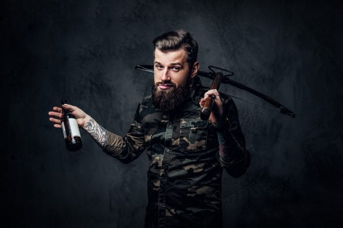 Stylish Bearded Hipster Man In Military Shirt Holding A Crossbow